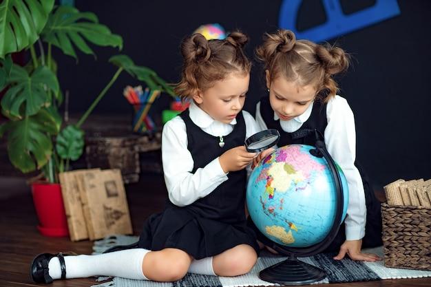 Tweelingen die bol met meer magnifier onderzoeken