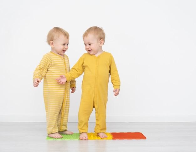 Tweelingen die zich op een kleurrijke mat bevinden