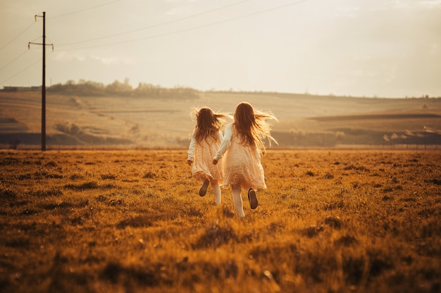 Tweelingen en beste vrienden die van de zomerzon genieten