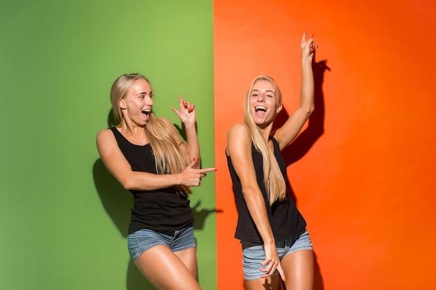 Tweelingen gelukkige vrouwen staan en glimlachen