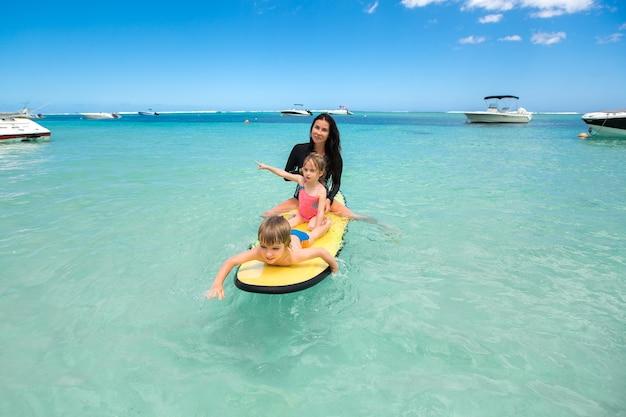 Tweelingen, jongen en meisje met moeder die in de oceaan op een schoolbord surfen