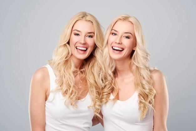 Tweelingen lachen op de grijze achtergrond