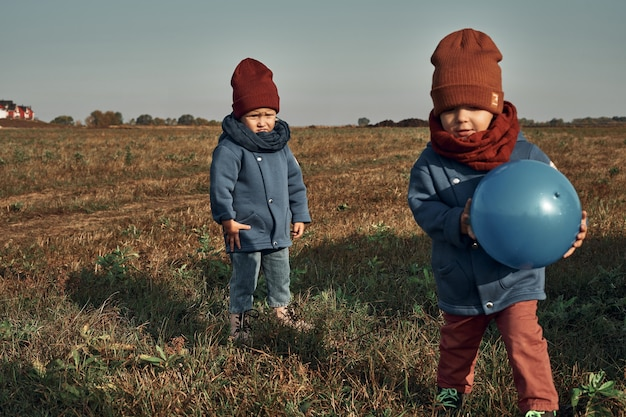 Tweelingen spelen een bal in het veld, een vuurtoren op de achtergrond, kinderen van twee jaar oud. herfstwandelingen in de natuur.