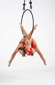 Tweelingen vrouwelijke circusartiest op de luchtfoto hoepel geïsoleerd op wit. zeer flexibele en professionele gymnasten.