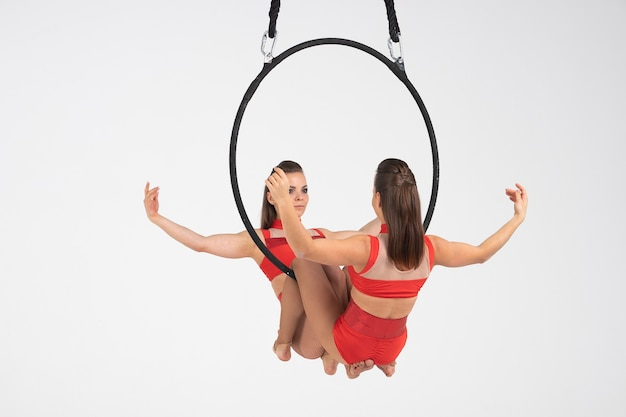 Tweelingen vrouwelijke circusartiest op de luchtfoto hoepel geïsoleerd op wit