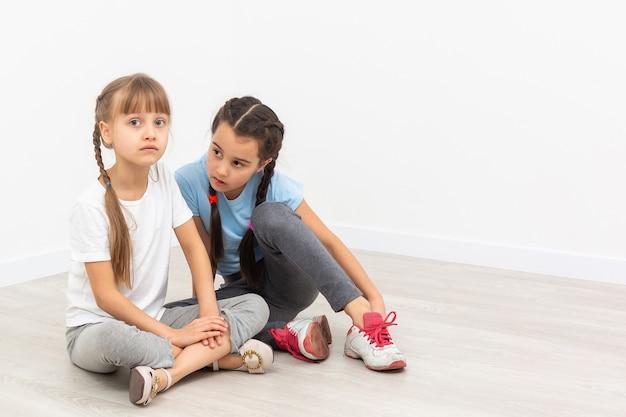 Tweelingenmeisjes zijn verdrietig, eenzaam en humeurig. kinderen zijn alleen, verdrietig en gefrustreerd, kijkend naar de camera