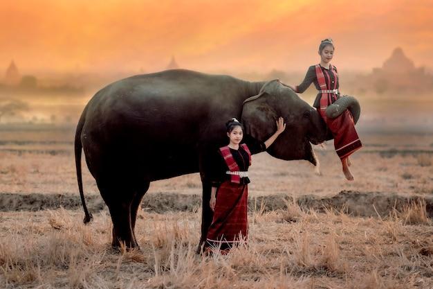 Tweelingmeisjes in het kuay-stamkostuum spelen met olifanten in de ochtend in surin, thailand.