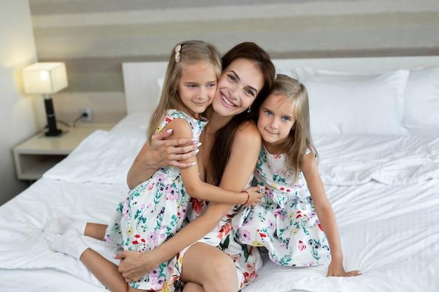 Tweelingmeisjes knuffelen hun moeder in een hotelkamer
