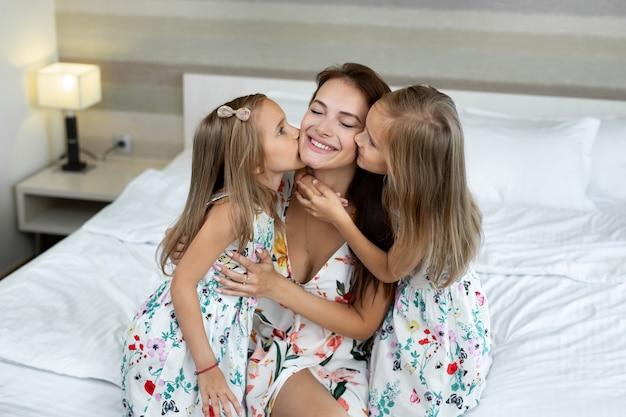 Tweelingmeisjes kussen hun moeder in een hotelkamer