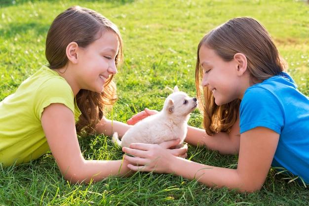 Tweelingzus kid meisjes en puppy hondje liggend in het gazon