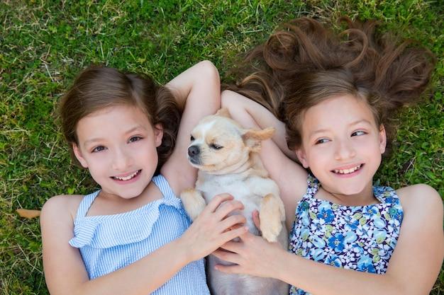 Tweelingzusjes spelen met chihuahua hond liggend op het gazon