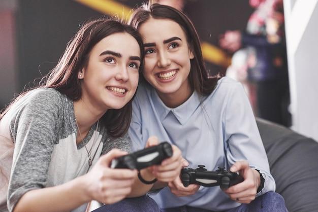 Tweelingzusjes spelen op de console. meisjes houden joysticks in hun handen en hebben plezier