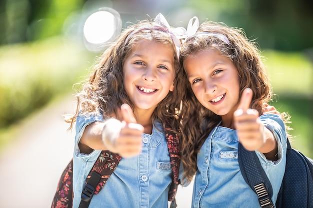 Tweelingzussen gaan terug naar school en laten hun duimen zien.
