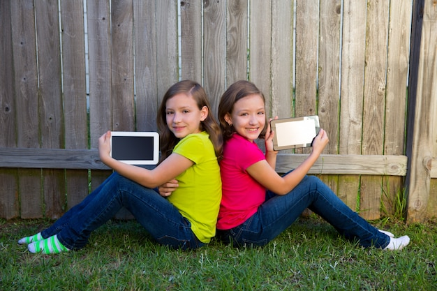 Tweelingzustermeisjes die de zitting van tabletpc op binnenplaatsgras spelen