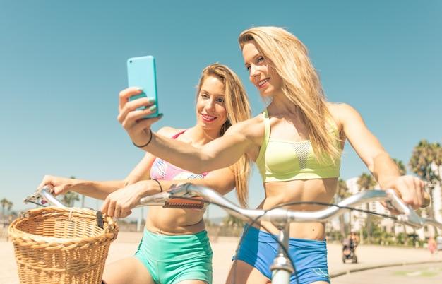 Tweelingzusters die selfie in los angeles op de strandgang nemen