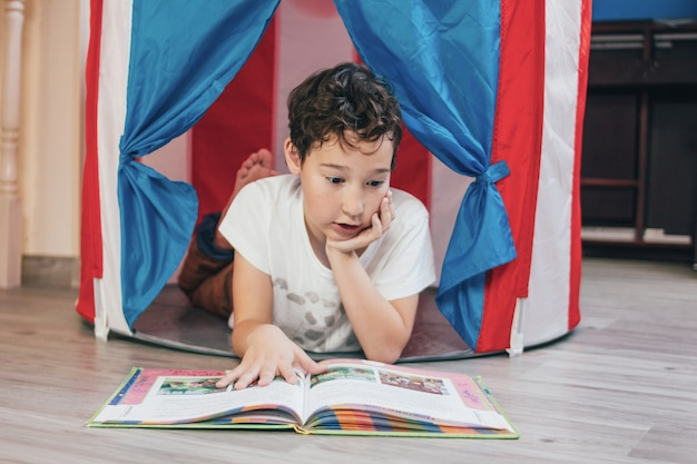 Tween denkende jongen met krullend haar in stuk speelgoed tenthuis die en boek thuis liggen lezen
