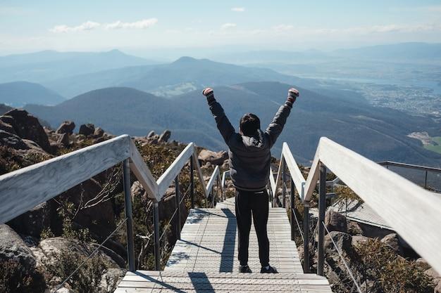 Tween jongen die met hand bovenop de berg, preteen-reisconcept, verwezenlijking en prestatie voor tiener opstaan
