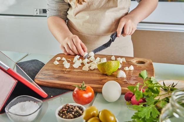 Tween koken volgens de tutorial van online virtuele masterclass, en kijken naar het digitale recept, touchscreen tablet gebruiken terwijl je thuis een gezonde maaltijd kookt in de keuken.