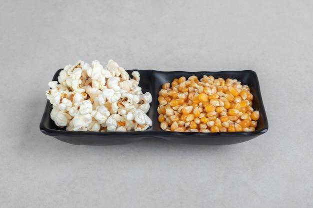 Tweezijdige serveerschaal met maïskorrels en popcorn op marmeren tafel.