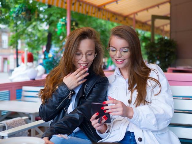 Twi meisjes delen geheimen, zittend in een café.