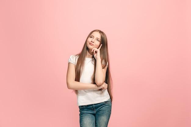 Twijfel concept. twijfelachtig, attent tienermeisje dat zich iets herinnert. menselijke emoties, gezichtsuitdrukking concept. tiener poseren in studio op roze achtergrond