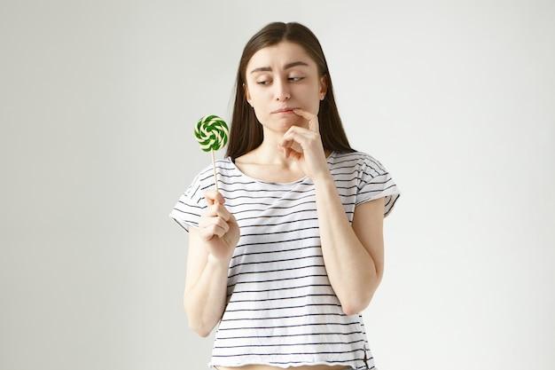 Twijfelachtig besluiteloos jonge europese donkerharige vrouw in vrijetijdskleding bijtende vinger als ze kijkt naar kleurrijke lolly in haar hand, aarzelt om het op te eten vanwege een gezond suikervrij dieet