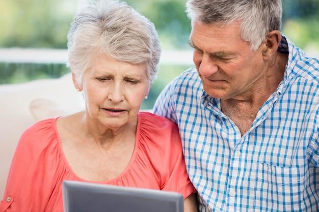 Twijfelachtig hoger paar die tablet op de bank gebruiken