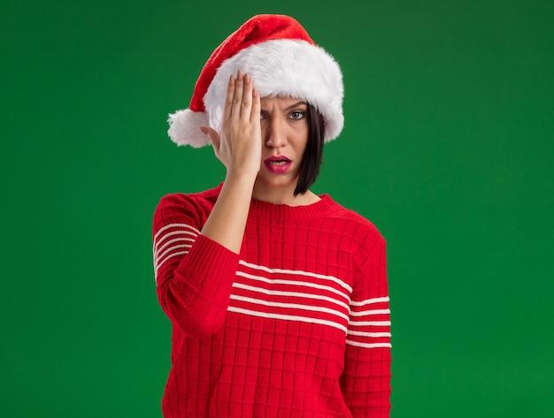 Twijfelachtig jong meisje dat santahoed draagt die de helft van gezicht behandelt met hand die op groene muur met exemplaarruimte wordt geïsoleerd