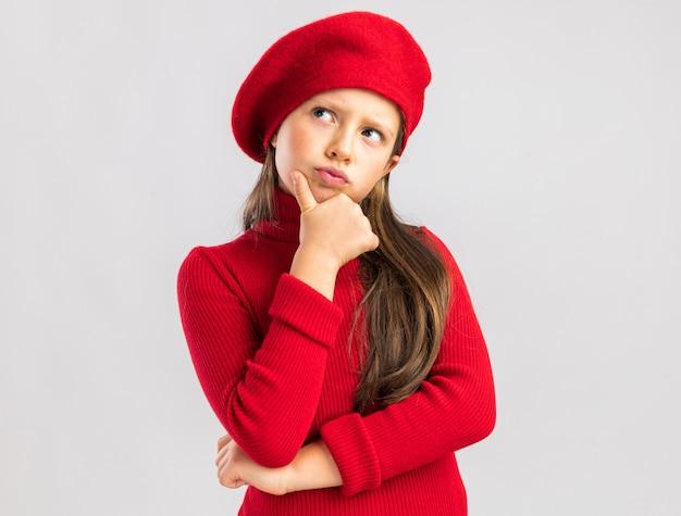 Twijfelachtig klein blond meisje met een rode baret die de hand op de kin houdt en naar de kant kijkt geïsoleerd op een witte muur met kopieerruimte