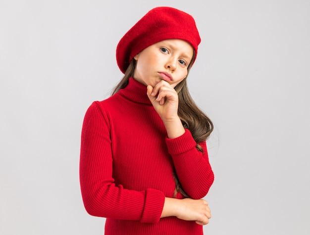 Twijfelachtig klein blond meisje met een rode baret die de hand op de kin houdt, geïsoleerd op een witte muur met kopieerruimte