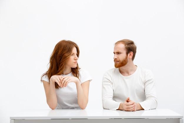 Twijfelachtig meisje en man kijken elkaar ongelovig aan