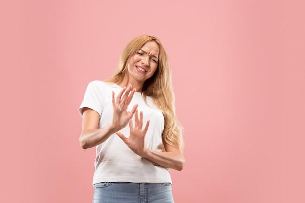 Twijfelachtig peinzende vrouw met doordachte expressie die keuze maakt tegen roze muur