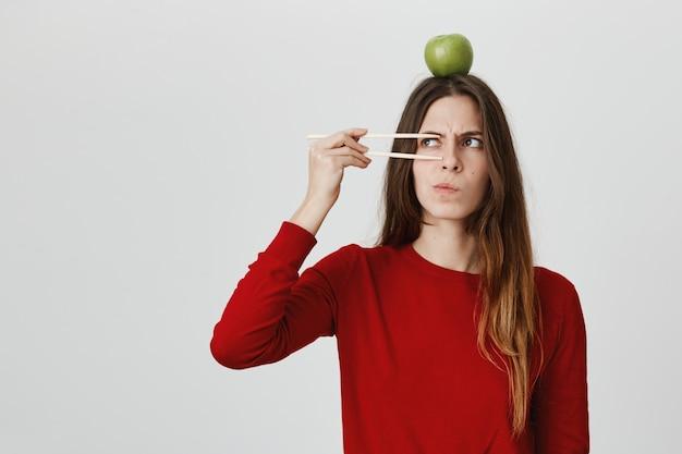 Twijfelachtig serieus ogend mooi meisje dat denkt en fronst met appel op hoofd en eetstokjes