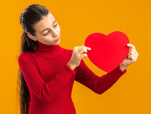 Twijfelachtig tienermeisje houdt en kijkt naar hartvorm met getuite lippen geïsoleerd op oranje muur