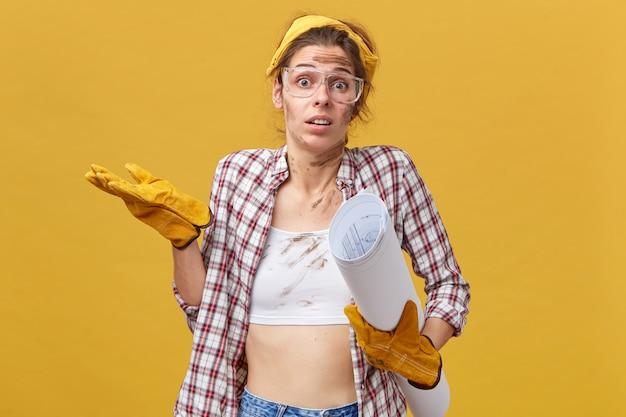 Twijfelachtig vrouwelijke ingenieur handwerk schouderophalend met onzekerheid doet. vuile vrouw met beschermende brillen, geruit overhemd en gele handschoenen die blauwdruk houden.