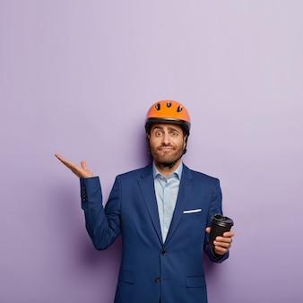 Twijfelachtig zakenman poseren in stijlvol pak en rode helm op kantoor