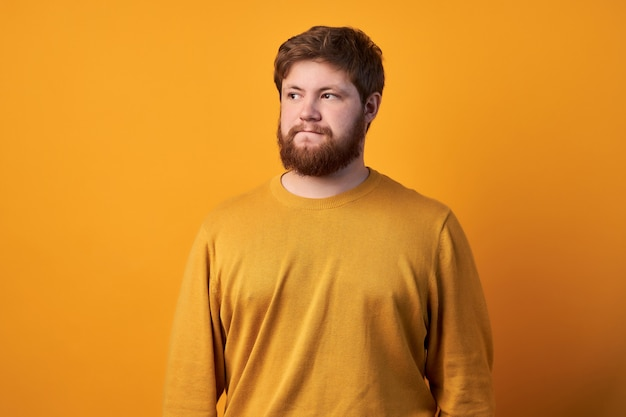 Twijfelachtige aarzelende man met rood haar en baard, sluit één oog en kijkt met een onnozele uitdrukking, maakt moeilijke keuze, geconcentreerd omhoog gekleed in geruit overhemd, staat tegen muur