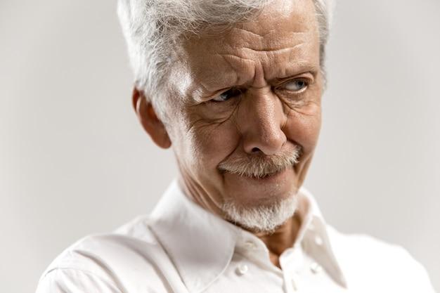 Twijfelachtige, bedachtzame man die zich iets herinnert. senior emotionele man. menselijke emoties, gezichtsuitdrukking concept. geïsoleerd op grijs