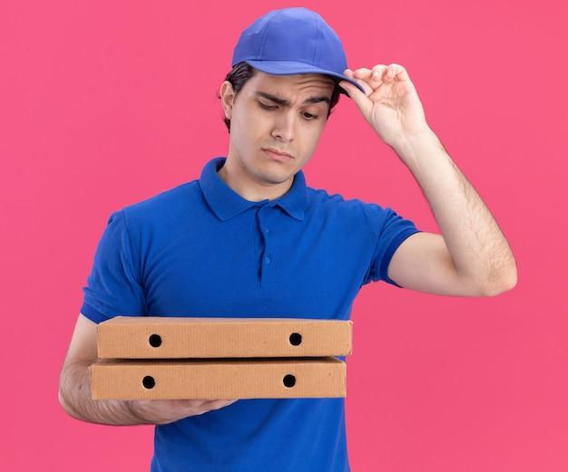 Twijfelachtige jonge blanke bezorger in blauw uniform en pet die pizzapakketten vasthoudt en kijkt en zijn pet vastpakt geïsoleerd op roze muur
