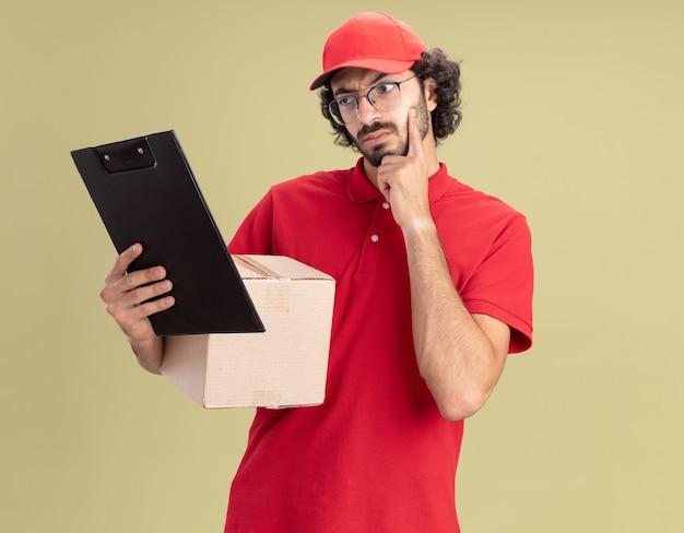 Twijfelachtige jonge blanke bezorger in rood uniform en pet met bril met kartonnen doos en klembord kijkend naar klembord met hand op kin geïsoleerd op olijfgroene muur