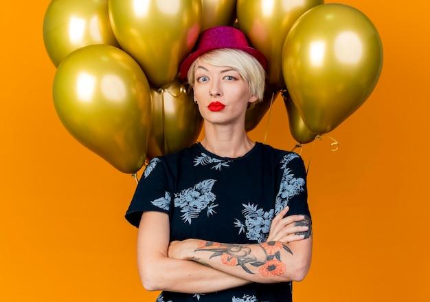 Twijfelachtige jonge blonde partijvrouw die partijhoed draagt die zich voor ballons met gesloten houding bevindt die voorzijde bekijken die op oranje muur wordt geïsoleerd