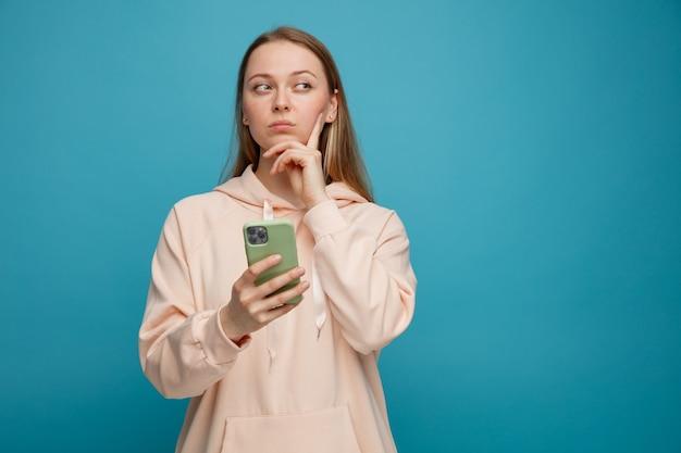 Twijfelachtige jonge blonde vrouw die mobiele telefoon houdt die hand op kin houdt die kant bekijkt