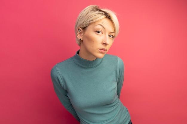 Twijfelachtige jonge blonde vrouw die naar de voorkant kijkt en de handen achter de rug houdt geïsoleerd op een roze muur met kopieerruimte