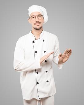 Twijfelachtige jonge chef-kok die een gebaar doet van kalmte bewaren