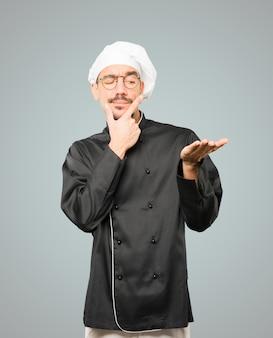 Twijfelachtige jonge chef-kok die iets met zijn hand houdt