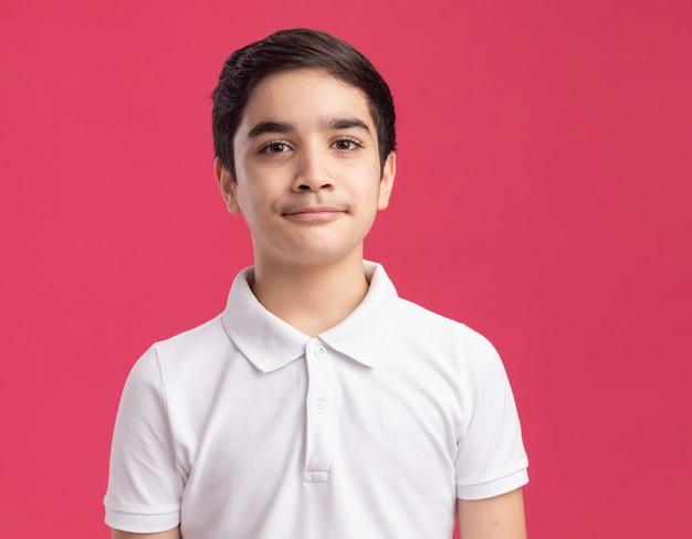 Twijfelachtige jonge jongen die naar voren loensende ogen kijkt die op roze muur worden geïsoleerd