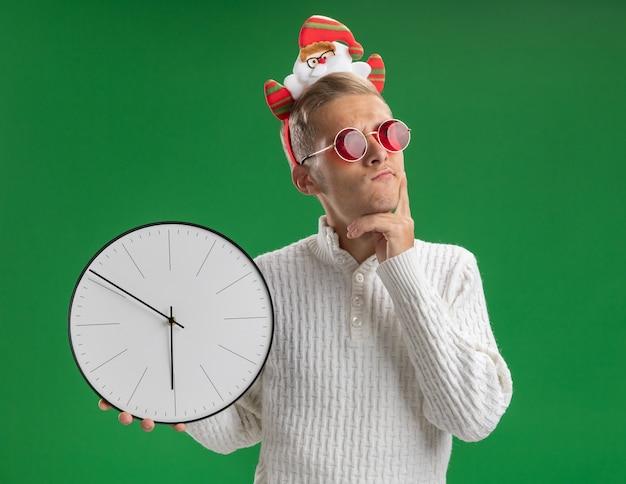 Twijfelachtige jonge knappe kerel die de hoofdband van de kerstman met een bril draagt die klok houdt die hand op kin houdt die kant bekijkt die op groene muur wordt geïsoleerd