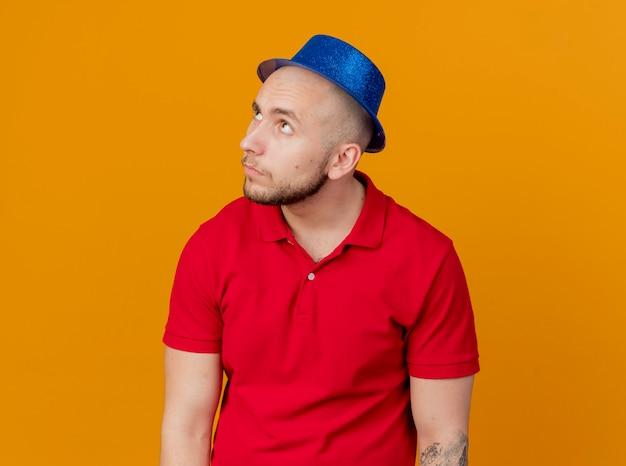 Twijfelachtige jonge knappe partijkerel die partijhoed draagt die hoofd aan kant draait die omhoog geïsoleerd op oranje muur kijkt