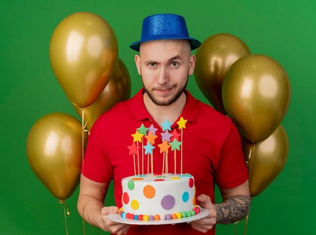 Twijfelachtige jonge knappe partijkerel die partijhoed draagt die zich voor ballons houdt die verjaardagstaart bekijkt die voorzijde bekijkt die op groene muur wordt geïsoleerd