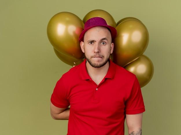 Twijfelachtige jonge knappe slavische partij kerel met feestmuts met ballonnen achter rug lip bijten kijken camera geïsoleerd op olijfgroene achtergrond met kopie ruimte